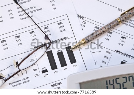 Financial reports with pen, glasses, and a calculator - stock photo
