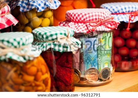 Financial reserves. Money conserved in a glass jar among others preserves. Shallow deep of focus. - stock photo