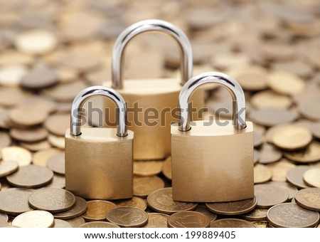 Financial security. Golden coins and padlocks. - stock photo