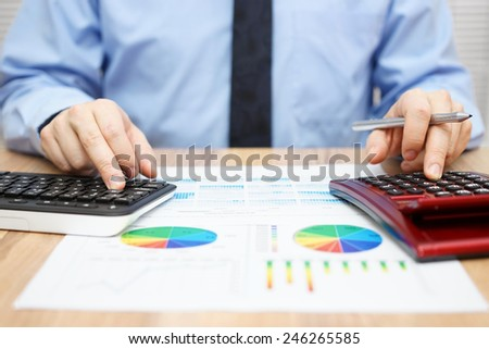 financial specialist is working with calculator and computer to analyze a lot of data on financial report - stock photo