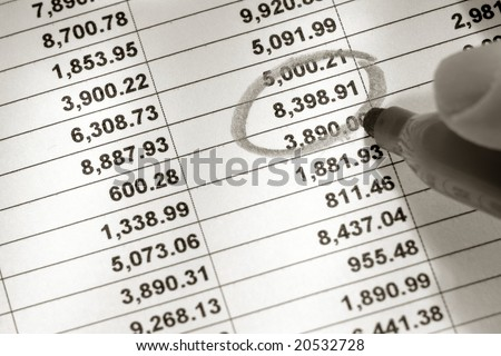 Financial spreadsheet with columns and rows of dollar figures numbers with one single number being circled with marker held in fingers