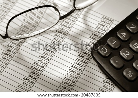 Financial spreadsheet with Dollar number figures in boxed rows and columns with calculator and glasses