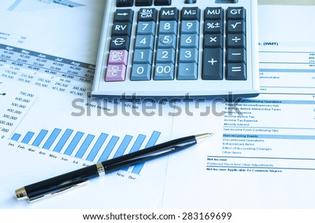 Financial statement analysis with pen and calculator - stock photo