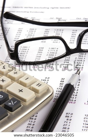 Financial statement with calculator, eyeglasses and fountain pen.