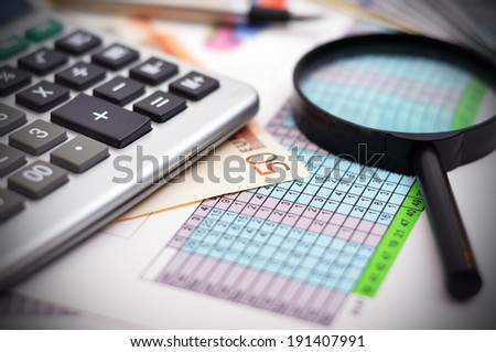 financial table with calculator and magnifying glass - stock photo