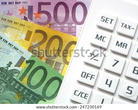 Financial transactions Euro bills lying next to a calculator - stock photo