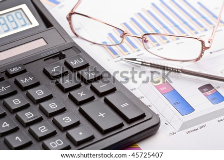 Financial work. The calculator, pen and female eyeglasses on business reports