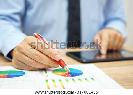financial worker analyzing business data and working with tablet computer - stock photo