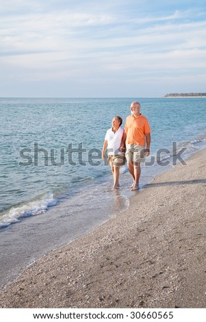 Financially secure retired senior couple enjoys a walk on a beautiful beach.  Wide angle view with room for text. - stock photo