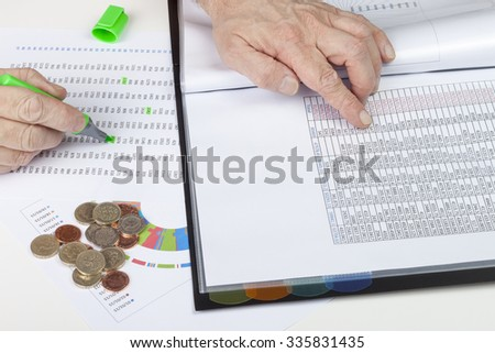 Financier at desk cross referencing some sales ledgers - stock photo