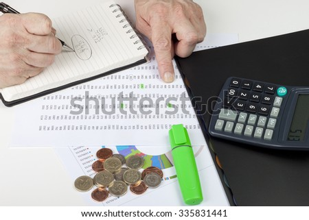Financier referencing a spreadsheet with a calculator - stock photo