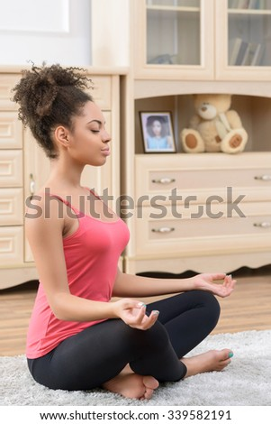 Find harmony. Pleasant peaceful young curly girl sitting on the floor and closing her eyes while practicing  yoga