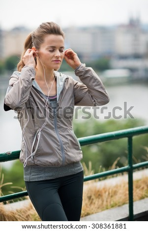 Find that beat, find that motivation... A woman holds her earbuds into her ears, eyes closed, and lost in the rhythm of her music. Waiting for just the right beat to hit her stride while running. - stock photo
