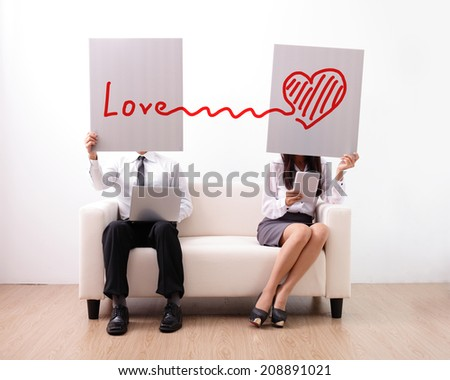 Find ture love on internet - man and woman using computer and digital tablet on sofa - stock photo