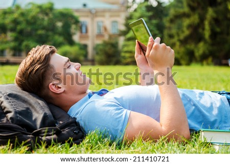 Finding a peaceful place to relax. Side view of handsome young man working on digital tablet while lying on grass  - stock photo