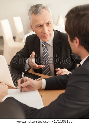 Finding a solution. Two business people in formalwear discussing something while sitting at the table - stock photo