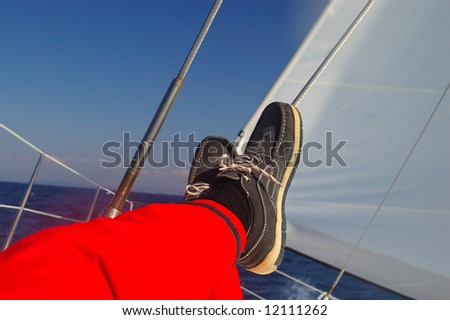 Finding comfortable position at sailing - legs resting - stock photo