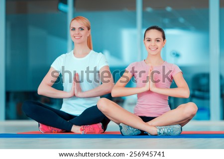 Finding inner peace and harmony. Beautiful teenage girl and her mother in sports clothing training yoga and taking similar positions on the mat in sports club - stock photo