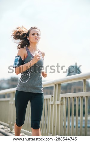 Finding my stride to the beat of the drums... An athletic woman hits her stride as she jogs on a bridge above an urban river. She is concentrating and in the groove. Working out feels great. - stock photo