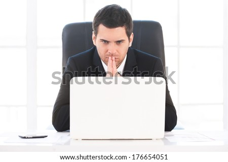 Finding out solution. Worried young man in formalwear looking at the computer and holding hands clasped while sitting at his working place - stock photo