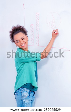 Finding the path to success. Young African woman in smart casual wear drawing diagram on the whiteboard while having a brainstorming  - stock photo