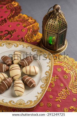 Fine arabic date chocolates and ramadan lamp. - stock photo