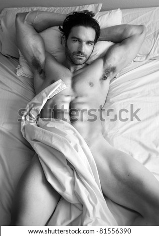 Fine art black and white body portrait of a nude male model in bed - stock photo