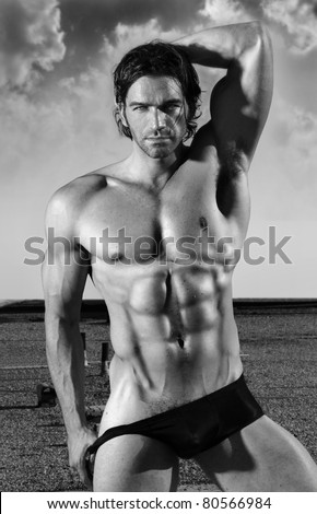 Fine art black and white portrait of a beautiful muscular male model in black briefs in provocative pose outdoors - stock photo