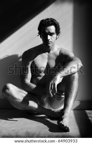 Fine art black and white sensual photo of a young man in underwear - stock photo