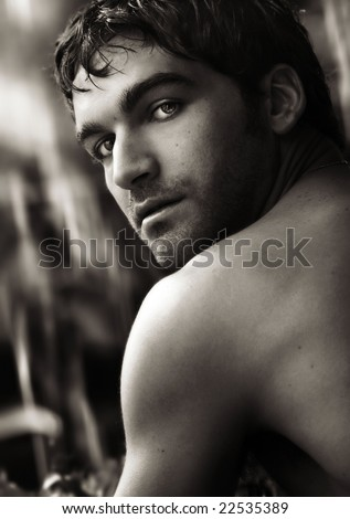 Fine art close-up black and white portrait of beautiful young man turning toward viewer - stock photo