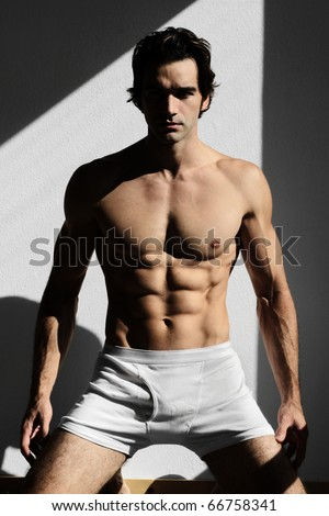 Fine art fashion portrait of a young muscular man in the shadows and light - stock photo