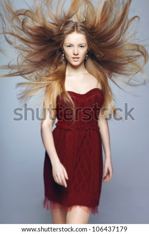 Fine art fashion portrait of blond fashion model posing with hair fluttering in the wind, shallow deep of field - stock photo