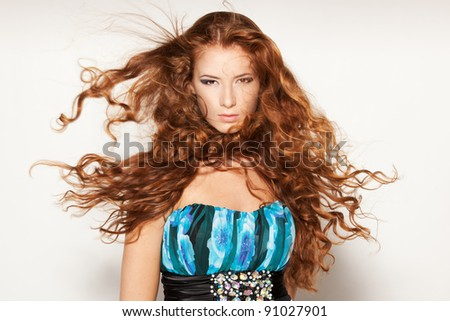 Fine art fashion portrait of red-haired fashion model posing with hair fluttering in the wind - stock photo