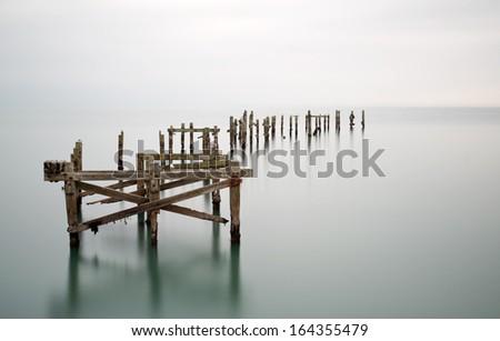 Fine art long exposure landscape of decayed pier - stock photo