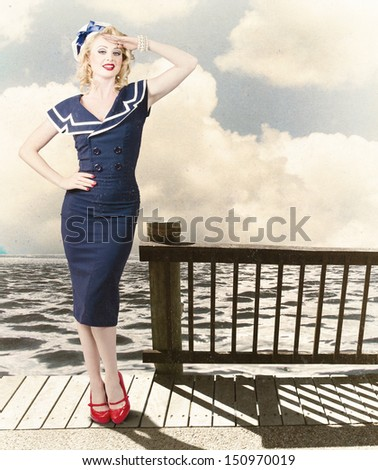Fine art photo of a beautiful young pin-up woman with vintage make-up and blond hairstyle saluting on vacation departure dock - stock photo