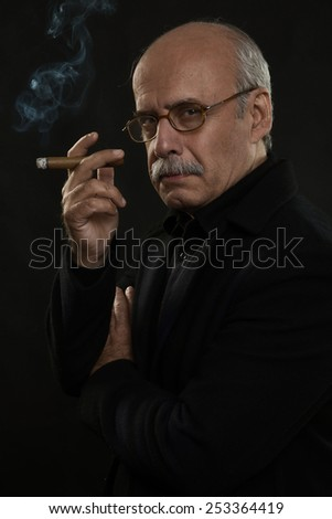 fine art portrait of a stylish old man smoking a cigar - stock photo