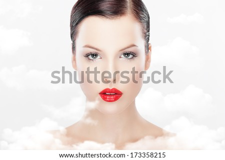 fine art portrait of beautiful naked young women with red lipstick. Retouched with special care.Clouds added to increase impact of purity. Heavenly beauty concept  - stock photo