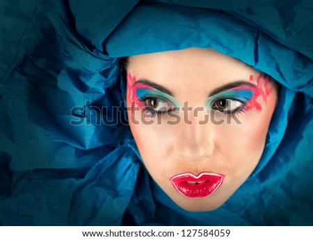 Fine art portrait of woman with colorful makeup in blue turban (looking away)