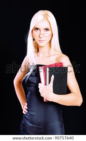 Fine blonde in glasses with book, it is isolated on black background. - stock photo