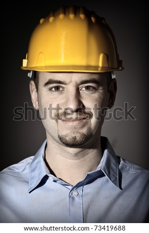 fine closeup portrait of young engineer with helmet