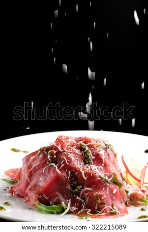 Fine dining, Beef carpaccio with pesto genovese, parmesan cheese, capers and rocket salad - stock photo