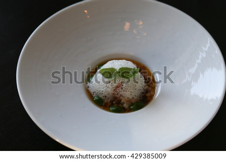 fine dining dish with foam soup and garnish - stock photo