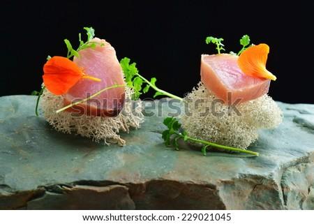 Fine dining, fresh raw ahi tuna sashimi served on sponge with herbs - stock photo