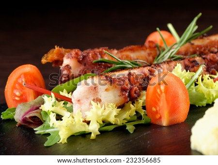 Fine dining, Grilled octopus with a salad - stock photo