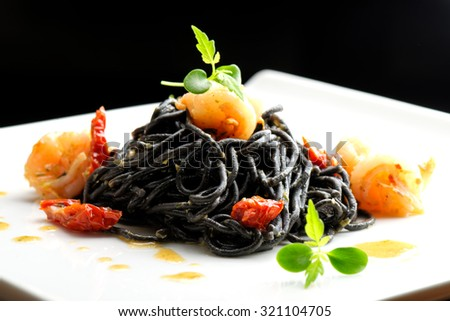 Fine dining, Italian squid ink pasta with shrimp basil selective focus - stock photo