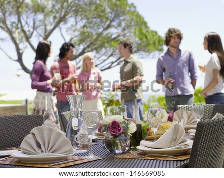 Fine dining table setting with friends enjoying drinks in background - stock photo