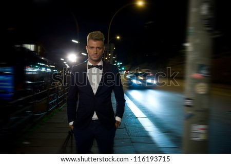 Fine dressed young men standing on the street at night - stock photo