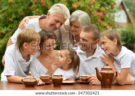 Fine family sitting on the veranda of their cottage - stock photo