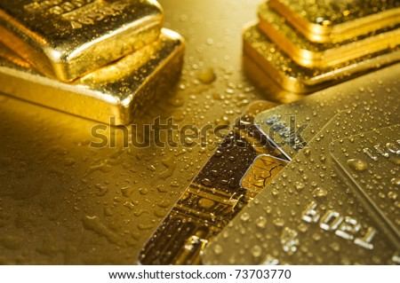 fine gold ingots and credit cards on a wet golden background - stock photo