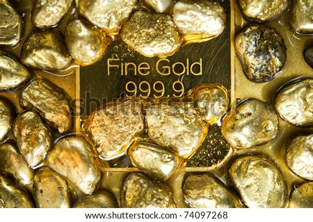 fine gold ingots and nuggets on a wet golden background - stock photo